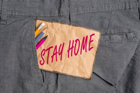Handwriting text writing Stay Home. Conceptual photo not go out for an activity and stay inside the house or home Writing equipment and brown note paper inside pocket of man work trousers