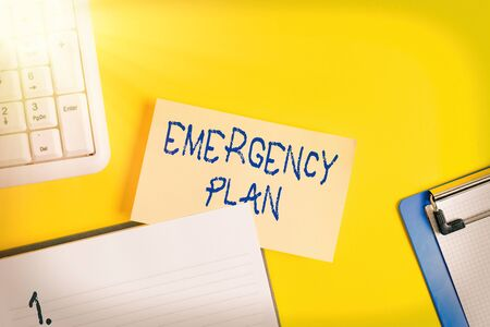 Writing note showing Emergency Plan. Business concept for procedures for handling sudden or unexpected situations Empty orange paper with copy space on the yellow table