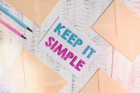 Writing note showing Keep It Simple. Business concept for ask something easy understand not go into too much detail Envelopes highlighters ruled paper sheet wooden vintage background