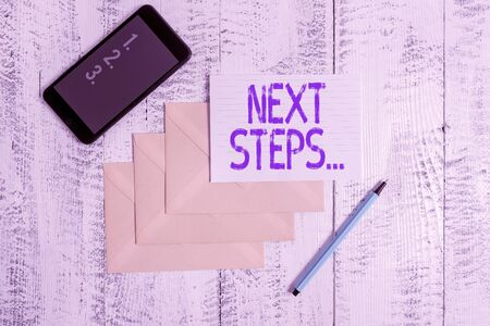 Conceptual hand writing showing Next Steps. Concept meaning something you do or plan after you ve finished something else Envelopes marker ruled paper smartphone wooden background Banco de Imagens