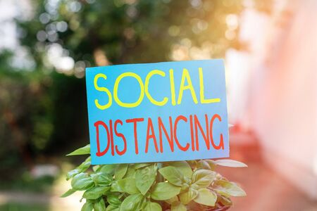 Writing note showing Social Distancing. Business concept for degree of acceptance of general interaction of individuals Plain paper attached to stick and placed in the grassy land