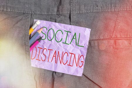 Conceptual hand writing showing Social Distancing. Concept meaning degree of acceptance of general interaction of individuals Writing equipment and purple note paper inside pocket of trousers