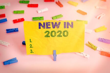 Handwriting text writing New In 2020. Conceptual photo what will be expecting or new creation for the year 2020 Colored clothespin papers empty reminder pink floor background office pin 免版税图像