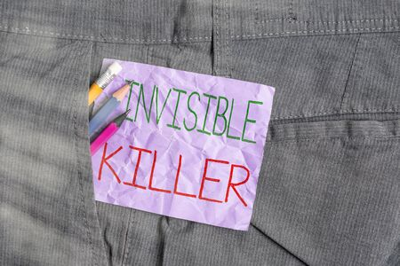 Conceptual hand writing showing Invisible Killer. Concept meaning presence into the air of a substance which are harmful Writing equipment and purple note paper inside pocket of trousers