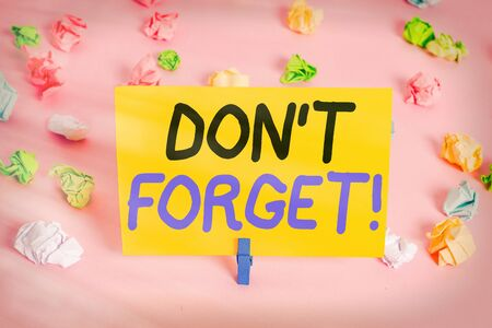 Text sign showing Don T Forget. Business photo text used to remind someone about an important fact or detail Colored crumpled papers empty reminder pink floor background clothespin
