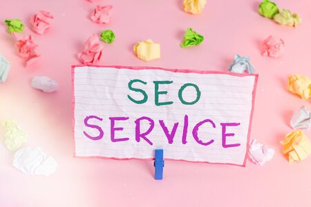 Text sign showing Seo Service. Business photo text techniques and procedures to increase the website visibility Colored crumpled papers empty reminder pink floor background clothespin
