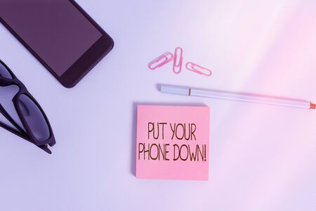 Writing note showing Put Your Phone Down. Business concept for end telephone connection saying goodbye caller Eyeglasses colored sticky note smartphone cell pen pastel background