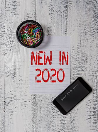 Handwriting text writing New In 2020. Conceptual photo what will be expecting or new creation for the year 2020 Smartphone paper sheet clips holder vintage wooden vintage old background 免版税图像