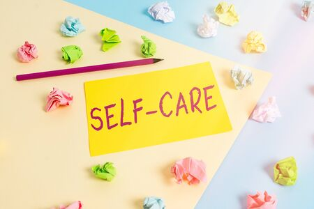 Handwriting text Self Care. Conceptual photo the practice of taking action to improve one s is own health Colored crumpled papers empty reminder blue yellow background clothespin Stock fotó