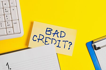 Writing note showing Bad Creditquestion. Business concept for inabilityof an individual to repay a debt on time and in full Empty orange paper with copy space on the yellow table
