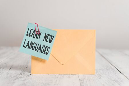 Text sign showing Learn New Languages. Business photo text developing ability to communicate in foreign lang Standing rectangular colored envelope sticky note clip wooden background