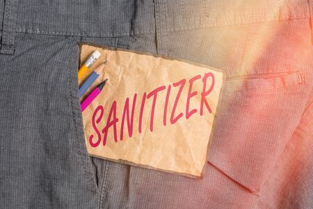 Handwriting text writing Sanitizer. Conceptual photo liquid or gel generally used to decrease infectious agents Writing equipment and brown note paper inside pocket of man work trousers