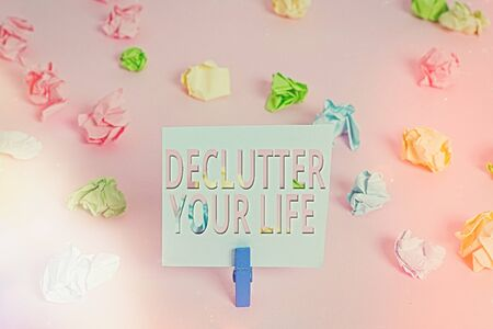 Word writing text Declutter Your Life. Business photo showcasing To eliminate extraneous things or information in life Colored crumpled papers empty reminder pink floor background clothespin Stok Fotoğraf