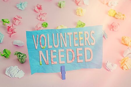 Word writing text Volunteers Needed. Business photo showcasing need work or help for organization without being paid Colored crumpled papers empty reminder pink floor background clothespin Imagens