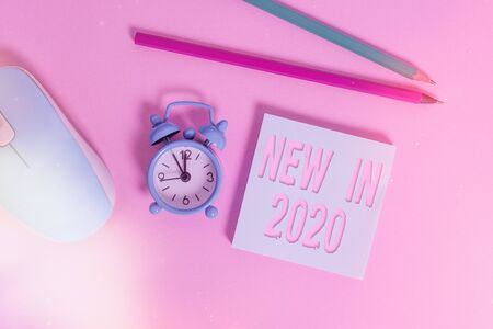 Text sign showing New In 2020. Business photo showcasing what will be expecting or new creation for the year 2020 Alarm clock wakeup blank notepad mouse markers colored background 免版税图像