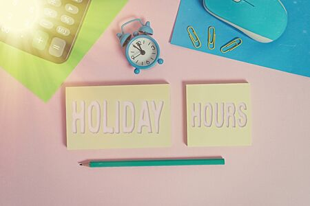 Handwriting text Holiday Hours. Conceptual photo employee receives twice their normal pay for all hours Wire mouse clock calculator notepads marker sheets clips color background