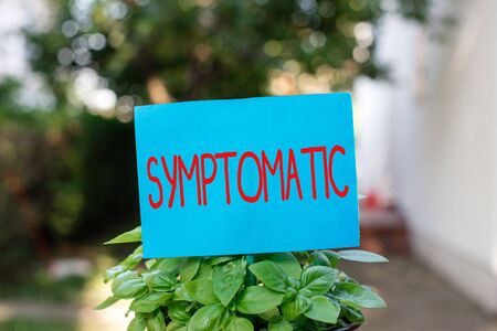 Writing note showing Symptomatic. Business concept for serving as symptom or sign especially of something undesirable Plain paper attached to stick and placed in the grassy land