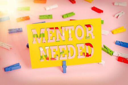 Text sign showing Mentor Needed. Business photo text wanted help for more experienced or more knowledgeable an individual Colored clothespin papers empty reminder pink floor background office pin