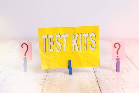 Writing note showing Test Kits. Business concept for tools used to detect the presence of something in the body Crumbling sheet with paper clips placed on the wooden table