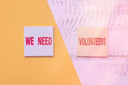 Text sign showing We Need Volunteers. Business photo showcasing someone who does work without being paid for it Two multicolor blank notepads colored paper sheet retro wooden background