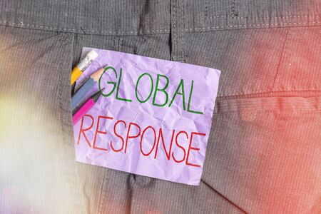 Conceptual hand writing showing Global Response. Concept meaning indicates the behaviour of material away from impact point Writing equipment and purple note paper inside pocket of trousers