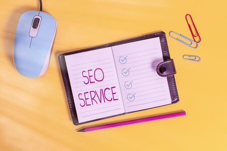 Writing note showing Seo Service. Business concept for techniques and procedures to increase the website visibility Leather locked diary striped sheets marker mouse colored background