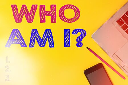 Handwriting text Who Am I Question. Conceptual photo asking about self identity or an individualal purpose in life Slim trendy silver open laptop pencil marker smartphone colored background