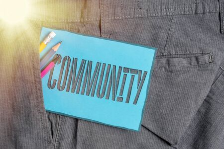 Conceptual hand writing showing Community. Concept meaning specific population with a common characteristics living together Writing equipment and blue note paper in pocket of trousers