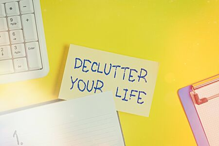 Writing note showing Declutter Your Life. Business concept for To eliminate extraneous things or information in life Empty orange paper with copy space on the yellow table
