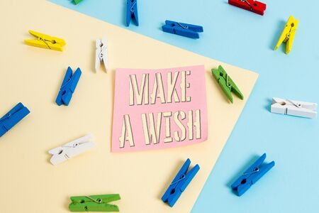 Writing note showing Make A Wish. Business concept for to desire a situation that is different from the one that exist Colored clothespin paper reminder with yellow blue background Banque d'images