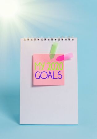 Handwriting text My 2020 Goals. Conceptual photo setting up an individualal goals or plans for the current year Standing spiral blank notebook sticky note banners cool pastel background
