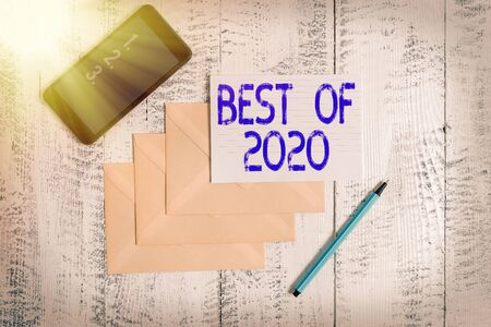 Conceptual hand writing showing Best Of 2020. Concept meaning great and marvelous things and events happened on 2020 Envelopes marker ruled paper smartphone wooden background