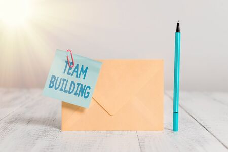 Conceptual hand writing showing Team Building. Concept meaning various types of activities used to enhance social relations Standing envelope sticky note marker old wooden vintage background
