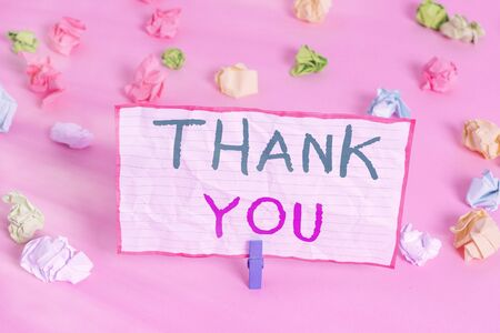 Text sign showing Thank You. Business photo text a polite expression used when acknowledging a gift or service Colored crumpled papers empty reminder pink floor background clothespin Banque d'images