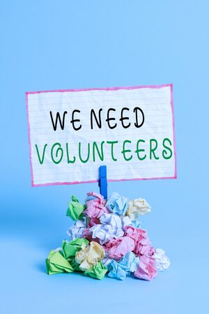 Conceptual hand writing showing We Need Volunteers. Concept meaning someone who does work without being paid for it Reminder pile colored crumpled paper clothespin wooden space