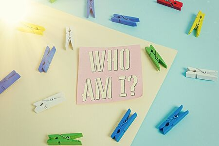 Writing note showing Who Am I Question. Business concept for asking about self identity or an individualal purpose in life Colored clothespin paper reminder with yellow blue background