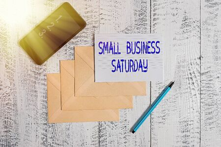 Conceptual hand writing showing Small Business Saturday. Concept meaning American shopping holiday held during the Saturday Envelopes marker ruled paper smartphone wooden background