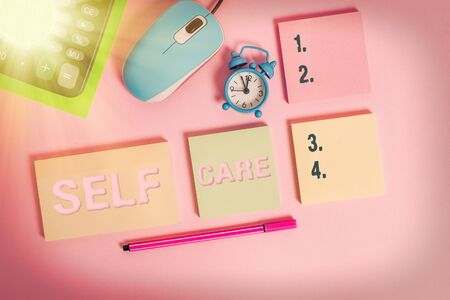 Handwriting text Self Care. Conceptual photo the practice of taking action to improve one s is own health Notepads mouse alarm clock calculator sheet marker colored background