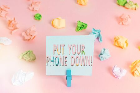 Word writing text Put Your Phone Down. Business photo showcasing end telephone connection saying goodbye caller Colored crumpled papers empty reminder pink floor background clothespin
