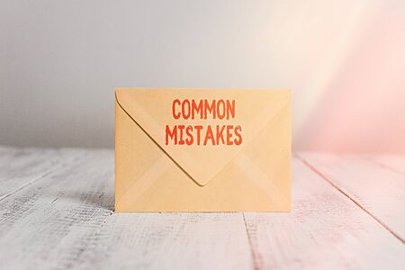 Handwriting text writing Common Mistakes. Conceptual photo actions that are often used interchangeably with error Closed standing rectangular colored envelope old wooden vintage background 免版税图像