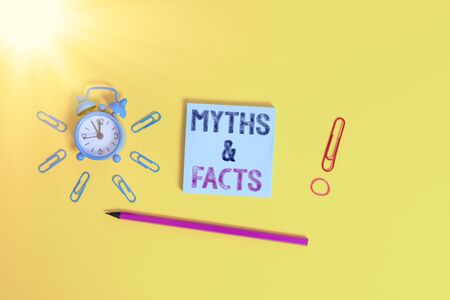 Writing note showing Myths And Facts. Business concept for usually traditional story of ostensibly historical events Alarm clock wakeup clips rubber band pencil notepad colored background