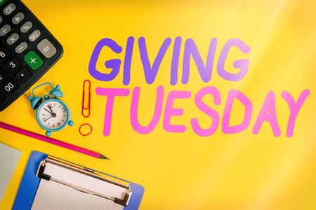Text sign showing Giving Tuesday. Business photo showcasing international day of charitable giving Hashtag activism Clock clips crushed note calculator pencil clipboard band color background Foto de archivo