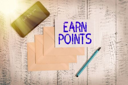 Conceptual hand writing showing Earn Points. Concept meaning getting praise or approval for something you have done Envelopes marker ruled paper smartphone wooden background