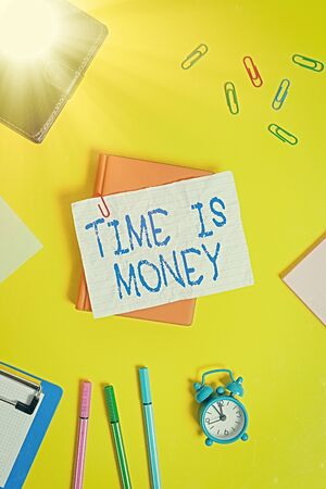 Writing note showing Time Is Money. Business concept for time is a valuable resource Do things as quickly as possible Flat lay above empty paper with pencils and paper clips 写真素材