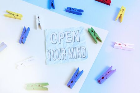 Handwriting text Open Your Mind. Conceptual photo to be able to understand different ideas or ways of thinking Colored clothespin paper empty reminder yellow blue floor background office
