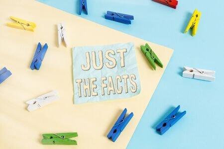 Handwriting text Just The Facts. Conceptual photo to have the correct information about the exact details Colored clothespin paper empty reminder yellow blue floor background office