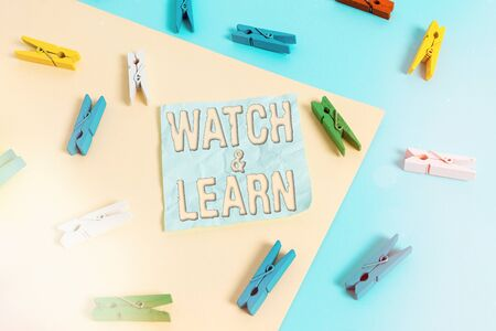 Handwriting text Watch And Learn. Conceptual photo demonstrating an action or ideas of how to do things Colored clothespin paper empty reminder yellow blue floor background office