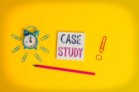Writing note showing Case Study. Business concept for analysis and a specific research design for examining a problem Alarm clock wakeup clips rubber band pencil notepad colored background