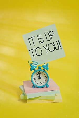 Handwriting text It Is Up To You. Conceptual photo Used to tell an individual that they are the one to decide Metal alarm clock blank sticky note stacked notepads colored background