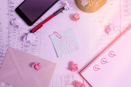 Conceptual hand writing showing Job Fair. Concept meaning event where employers offer information about their companies Smartphone sheet clips pen paper balls envelope wooden back